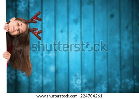 Festive little girl showing card against blurred snowflakes on planks - stock photo