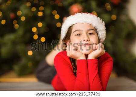 Festive little girl smiling at camera at home in the living room - stock photo