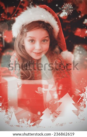 Festive little girl with gifts against candle burning against festive background - stock photo