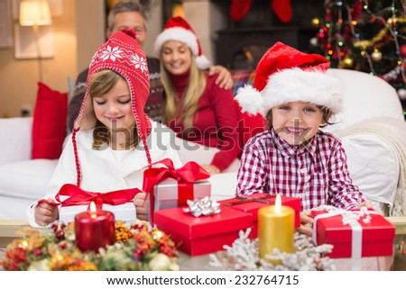 Festive little siblings opening a gift in front of their parents at home in the living room - stock photo