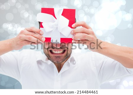 Festive man holding christmas gift against light glowing dots design pattern - stock photo