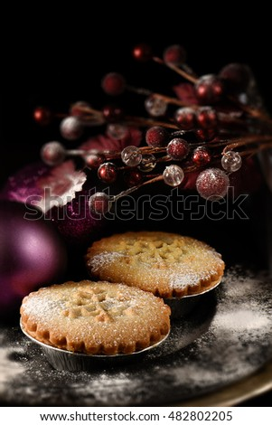 Festive mince pies against a dark background. the perfect image for your Christmas or Thanksgiving dessert menu cover design. Generous accommodation for copy space. Selective focus.