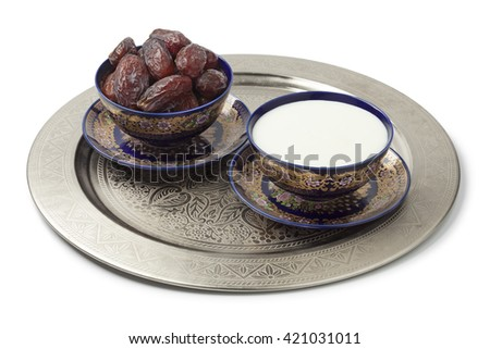 Festive Moroccan bowls with milk and dates on white background