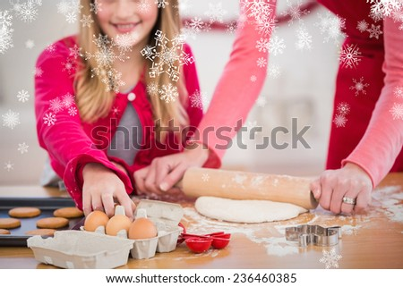 Festive mother and daughter making christmas cookies against snowflakes - stock photo