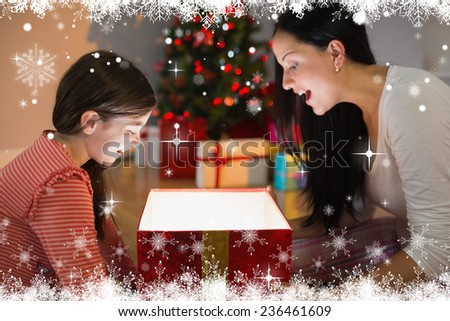 Festive mother and daughter opening a glowing christmas gift against fir tree forest and snowflakes - stock photo