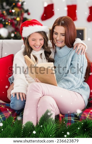 Festive mother and daughter reading on the couch against green fir branches with snow