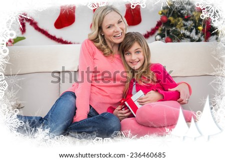 Festive mother and daughter smiling at camera against frost frame