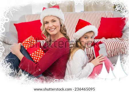 Festive mother and daughter smiling at camera with gifts against frost frame