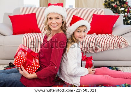 Festive mother and daughter smiling at camera with gifts at home in the living room