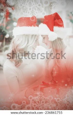 Festive mother and daughter smiling at each other against light design over floor boards - stock photo