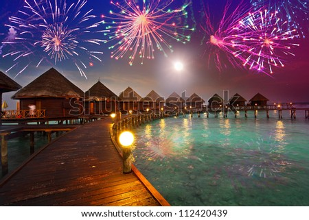 Festive New Year's fireworks over the tropical island - stock photo