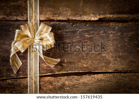 Festive ornamental gold ribbon and bow on a grunge rustic wood background with copyspace for your Christmas, anniversary or birthday wishes - stock photo