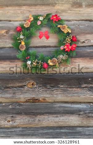 Festive outside X-mas spruce wreath at old grey log cabin wall background  - stock photo