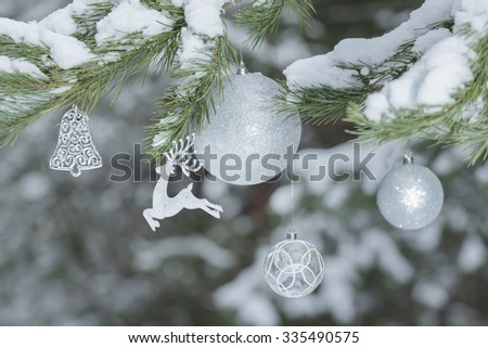 Festive pine tree branches with shiny reindeer ornament and Christmas baubles at snowy wood background - stock photo