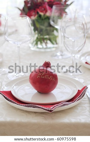 Festive place setting with pomegranate - stock photo