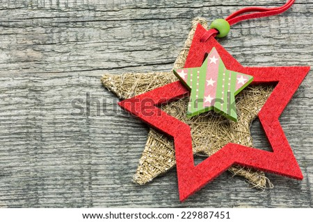 Festive red and gold stars on wood board with copy space - stock photo