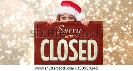Festive redhead smiling at camera holding poster against vintage closed sign - stock photo