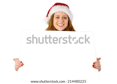 Festive redhead smiling at camera holding poster on white background