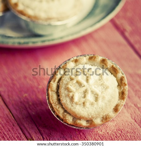 Festive shortcrust pastry mince pies. A sweet mince pie, a traditional rich festive food on red wooden background. - stock photo