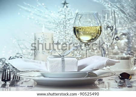 Festive silver dinner setting with gift for the holidays - stock photo