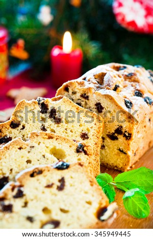 Festive sliced christmas fruitcake with raisins and mint leaf on christmas background. Indoors multicolored vertical close-up image.