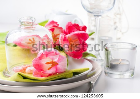 Festive spring table setting with pink tulips, napkins in bright colors - stock photo