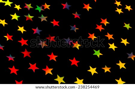 Festive starry background, many little colorful stars on black backdrop, beautiful Christmas decoration, festive wrapping paper - stock photo
