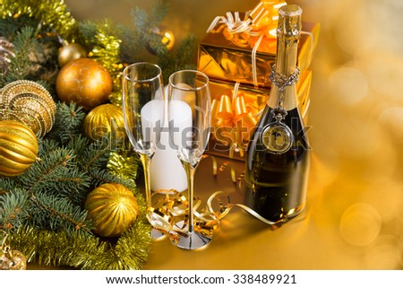 Festive Still Life - Antique Pocket Watch Draped on Bottle of Champagne with Pair of Glasses on Golden Background with Christmas Gifts and Evergreen Decorated with Gold Christmas Balls and Tinsel - stock photo