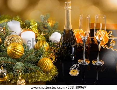Festive Still Life - Antique Pocket Watch with Bottle of Champagne and Glasses in front of Golden Background with Gifts, Candles and Evergreen Decorated with Christmas Balls and Tinsel - stock photo