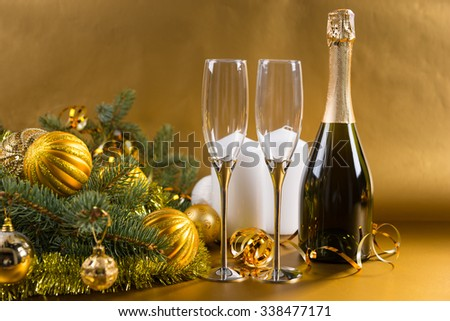 Festive Still Life of Elegant Glasses and Bottle of Champagne on Golden Background with White Pillar Candles and Evergreen Branches Decorated with Gold Christmas Balls and Tinsel - stock photo