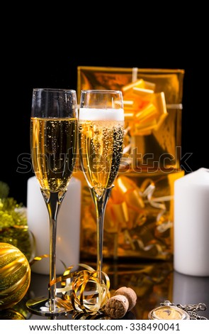 Festive Still Life - Pair of Glasses Filled with Sparkling Champagne in front of Black Background with Gold Wrapped Gifts, White Candles and Christmas Decorations - stock photo