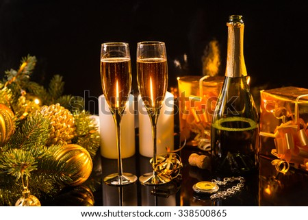 Festive Still Life - Two Glasses of Sparkling Champagne with Bottle, Candles, Gifts, Pocket Watch and Christmas Decorations on Black Background in Warm Lighting - stock photo