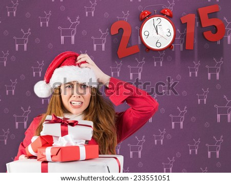 Festive stressed redhead holding gifts against purple reindeer pattern - stock photo