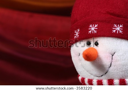 Festive stuffed Christmas snowman against a red background - stock photo