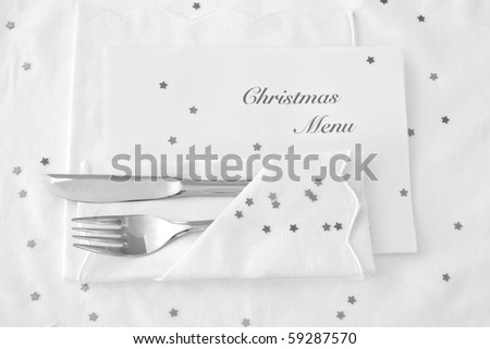 Festive table place setting for Christmas with shiny silver stars and menu - stock photo