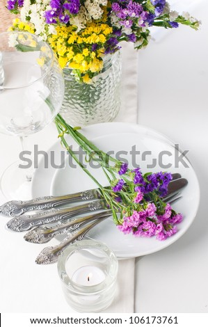 Festive table setting and decoration with fresh flowers - stock photo