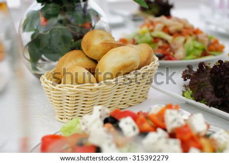 Festive table setting. Buns in a wicker basket. Banquet table, Serving dishes, Food restaurant.  Wedding evening. The peoples kitchen. A range of snacks. Decor with white tablecloth. Christmas table.  - stock photo