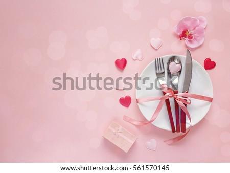 thiết lập cho Ngày Valentine với dao kéo, hoa lan, hộp quà tặng và những trái tim trên bàn hồng bảng lễ hội.  Không gian cho văn bản.  Top xem.