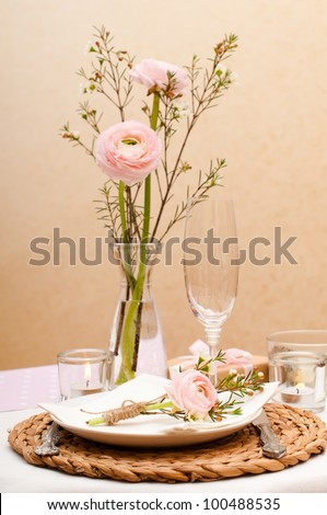 Festive table setting with pink flowers and candles - stock photo