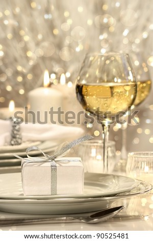 Festive table setting with silver ribbon gift on plate - stock photo