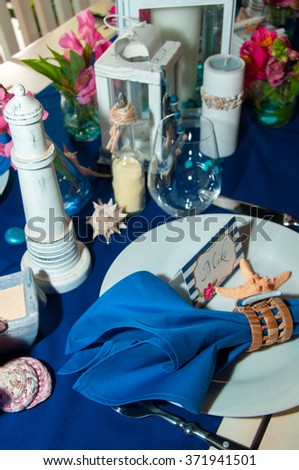 Festive table setting with starfishes, napkins, glasses and candles, bright summer table decor - stock photo