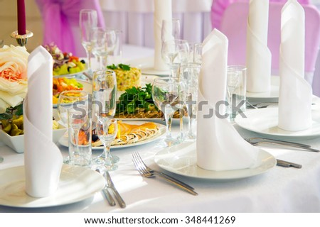 Festive table. Table setting. Festive round table with food.  Starched napkins and Cutlery. Festive meals. The restaurant inside. Service holidays. Design of the hall. - stock photo