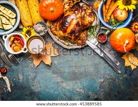 Festive  Thanksgiving Day food background with roasted whole turkey or chicken and sauce, harvest vegetables: corn, pumpkin,carrots with cutlery on dark rustic kitchen table, top view, border - stock photo