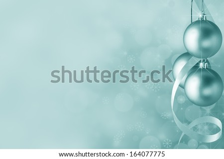 Festive turquoiser Christmas baubles and spiral streamer on the right. Circles of bokeh glow, sparkling stars and snowflakes in the background fading towards solid colour copy space on the left side. - stock photo