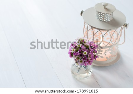 Festive wedding decor, bouquet of pink flowers and candle lantern on a white wooden board - stock photo