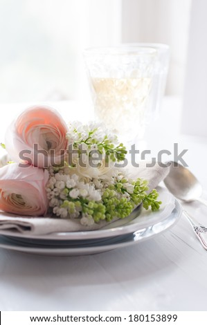 Festive wedding elegant dining table setting with a bouquet of flowers, buttercups and white lilac, and vintage cutlery on a white table - stock photo