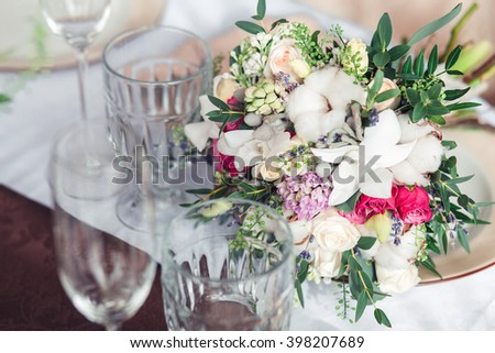 Festive wedding table setting with flowers, napkins, vintage cutlery, glasses, bright table decor details. - stock photo