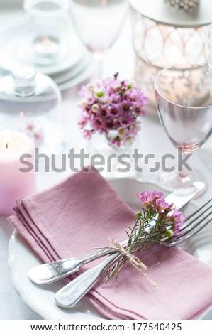 Festive wedding table setting with pink flowers, napkins, vintage cutlery, glasses and candles, bright summer table decor. - stock photo