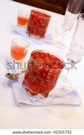 Festive winter white and red table with pomegranate-grapefruit jelly dessert - stock photo