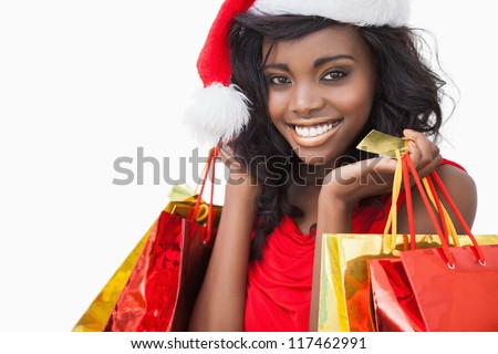 Festive woman standing looking while holding bags and smiling